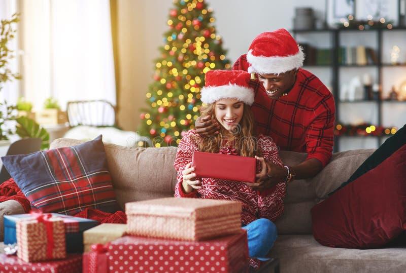 Το ευτυχές νέο άνοιγμα ζευγών παρουσιάζει στο πρωί Χριστουγέννων στοκ φωτογραφία