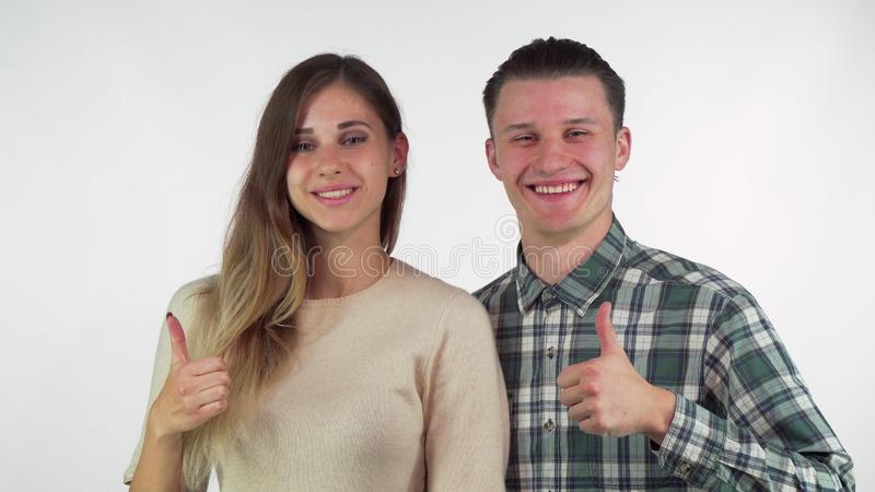 Το ευτυχές νέο αγαπώντας ζεύγος που χαμογελά στη κάμερα, παρουσίαση φυλλομετρεί επάνω στοκ εικόνες