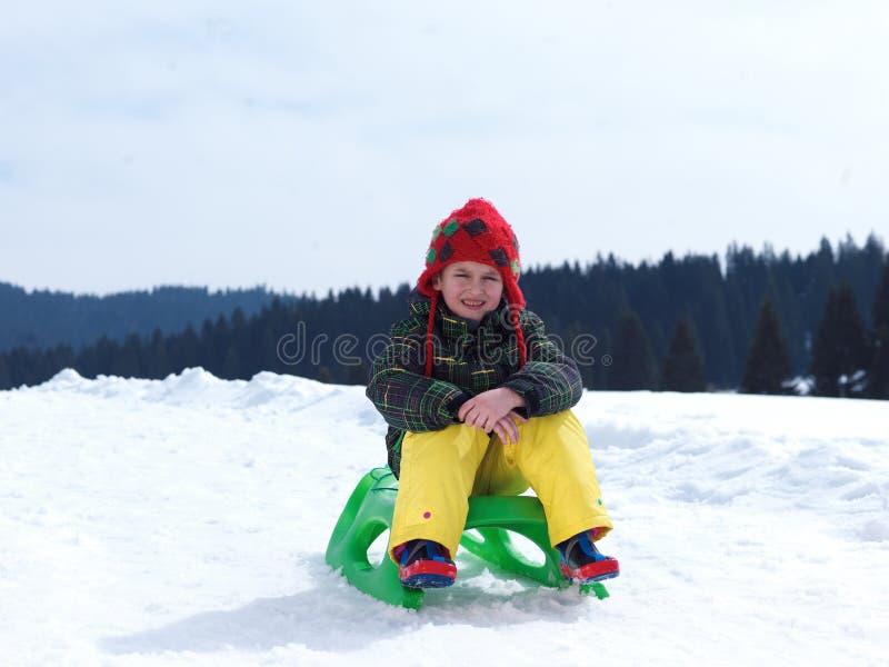 Το ευτυχές νέο αγόρι έχει τη διασκέδαση στο χειμώνα vacatioin στο φρέσκο χιόνι στοκ εικόνα με δικαίωμα ελεύθερης χρήσης