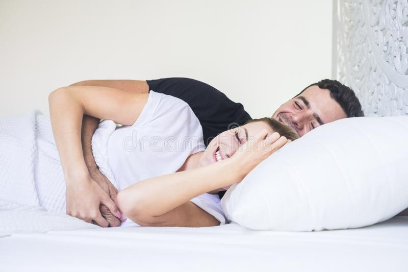 Το ευτυχές νέο ζεύγος καθορίζει και ύπνος ή να ξυπνήσει στα ξημερώματα στο σπίτι λευκιά κρεβατοκάμαρα στο σπίτι και άνθρωποι που  στοκ εικόνες
