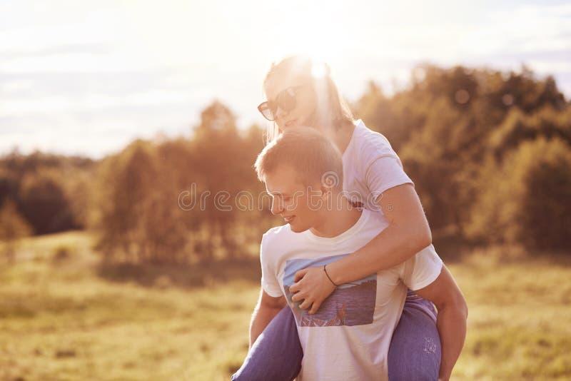 Το ευτυχές νέο ζεύγος ξοδεύει τον ελεύθερο χρόνο έξω, ο φίλος δίνει το σηκώνω στην πλάτη στη φίλη, θέτει στο υπόβαθρο φύσης, απολ στοκ εικόνες