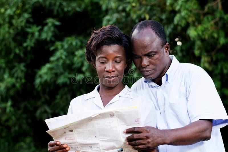 Το ευτυχές νέο ζεύγος που ταξιδεύει συμβουλεύεται έναν χάρτη στοκ φωτογραφία