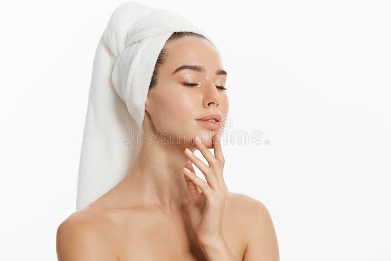 Το ευτυχές νέο κορίτσι με το καθαρό δέρμα και με μια άσπρη πετσέτα στο κεφάλι της πλένει το πρόσωπο στοκ φωτογραφία με δικαίωμα ελεύθερης χρήσης