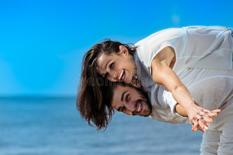 Το ευτυχές νέο ρομαντικό ζεύγος ερωτευμένο έχει τη διασκέδαση στην όμορφη παραλία στοκ εικόνα