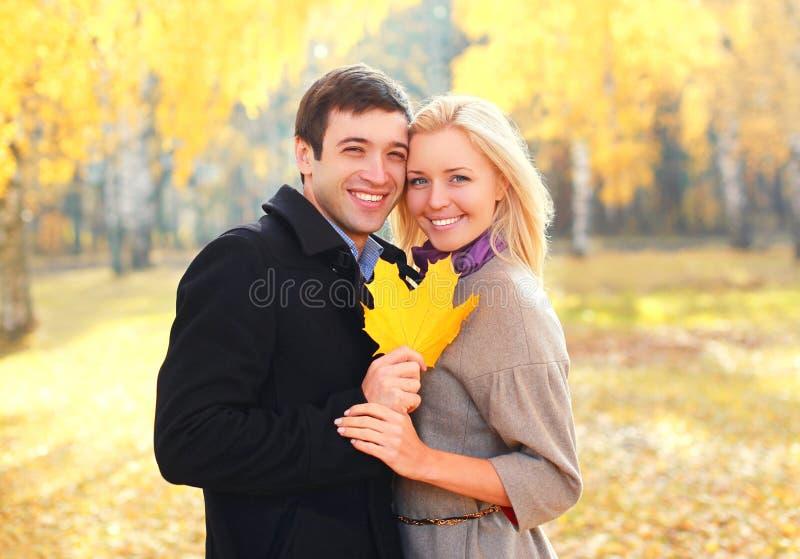 Το ευτυχές νέο χαμογελώντας ζεύγος πορτρέτου με τον κίτρινο σφένδαμνο βγάζει φύλλα θερμό σε ηλιόλουστο στοκ φωτογραφίες με δικαίωμα ελεύθερης χρήσης