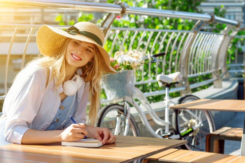 Το ευτυχές ξανθό κορίτσι κάνει τις σημειώσεις, μουσική ακούσματος και να ονειρευτεί στοκ φωτογραφία