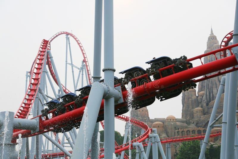 Το ευτυχές λούνα παρκ κοιλάδων επισκεπτών οδηγά rollercoaster στοκ εικόνες