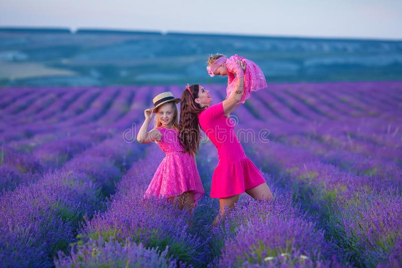 Το ευτυχές παιδί μητέρων και κορών μαζί με τα κίτρινα λουλούδια πικραλίδων στη θερινή ημέρα απολαμβάνει το ελεύθερο χρόνο διακοπώ στοκ φωτογραφία με δικαίωμα ελεύθερης χρήσης
