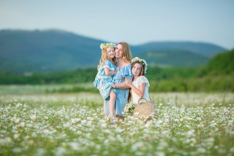 Το ευτυχές παιδί μητέρων και κορών μαζί με τα κίτρινα λουλούδια πικραλίδων στη θερινή ημέρα απολαμβάνει το ελεύθερο χρόνο διακοπώ στοκ φωτογραφίες
