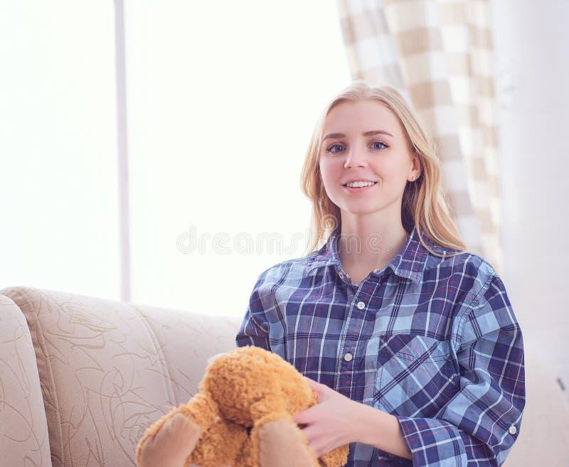 Το ευτυχές παιχνίδι έφηβη με Teddy αφορά τον καναπέ Είμαστε ευτυχείς να επανακτήσουμε την παιδική ηλικία μας στοκ φωτογραφία με δικαίωμα ελεύθερης χρήσης