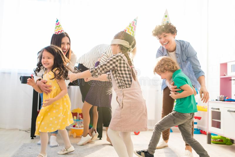 Το ευτυχές παιχνίδι γονέων τυφλό επανδρώνει στιλβωμένο με τα παιδιά τους στοκ φωτογραφία
