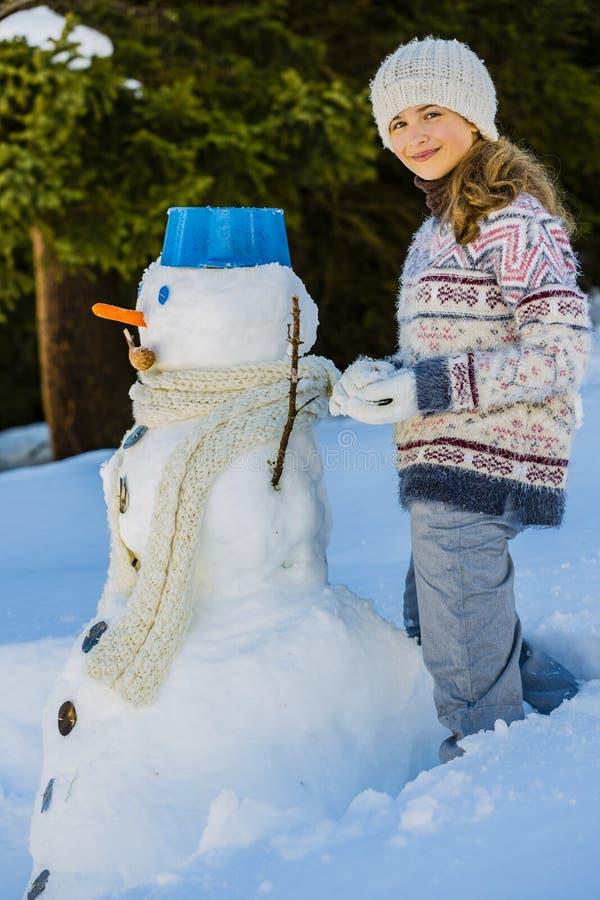 Το ευτυχές παιχνίδι έφηβη χαμόγελου με έναν χιονάνθρωπο σε έναν χιονώδη κερδίζει στοκ φωτογραφία