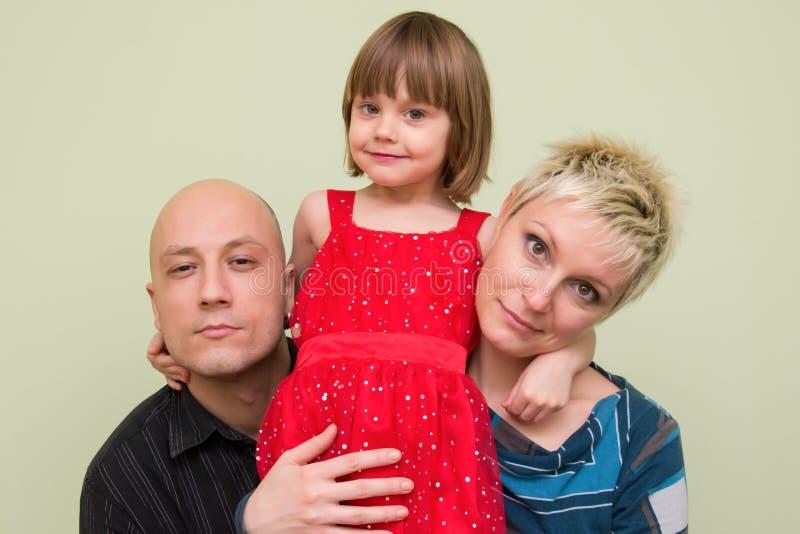 Το ευτυχές παιδί αγκαλιάζει τη μητέρα και τον πατέρα της στο σπίτι στοκ εικόνες