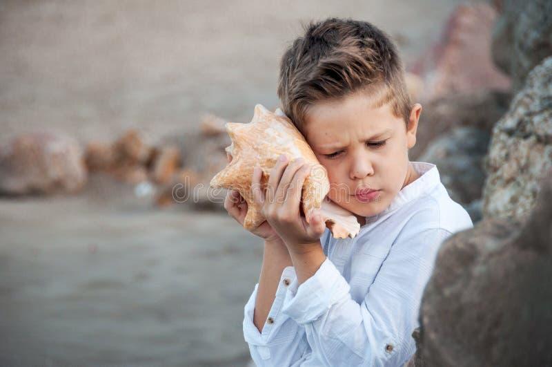 Το ευτυχές παιδί ακούει το θαλασσινό κοχύλι Έννοια διακοπών στοκ φωτογραφία με δικαίωμα ελεύθερης χρήσης