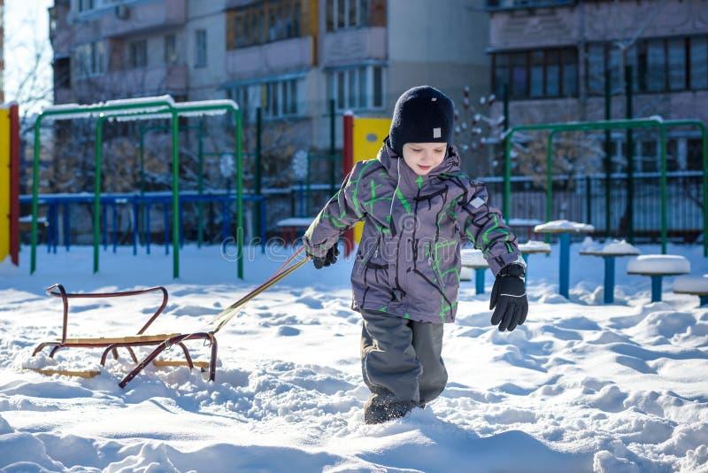 Το ευτυχές παιδί που περπατά υπαίθρια στη χειμερινή πόλη σέρνει το έλκηθρό του Παιδί που χαμογελά και που έχει τη διασκέδαση στοκ εικόνες