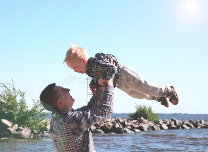 Το ευτυχές συγκινημένο παιχνίδι πατέρων και γιων στη θερινή παραλία, απολαμβάνει τη ζωή στοκ φωτογραφία με δικαίωμα ελεύθερης χρήσης
