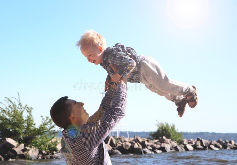 Το ευτυχές συγκινημένο παιχνίδι πατέρων και γιων στη θερινή παραλία, απολαμβάνει τη ζωή στοκ εικόνες