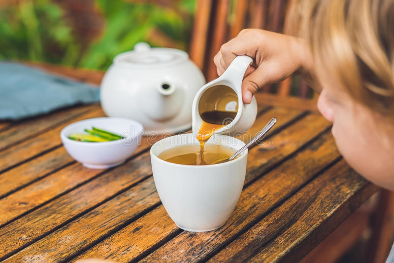 Το ευτυχές συμπαθητικό αγόρι χύνει το μέλι στο τσάι στο θερινό πράσινο κήπο Πορτρέτο υπαίθριος στοκ εικόνα με δικαίωμα ελεύθερης χρήσης