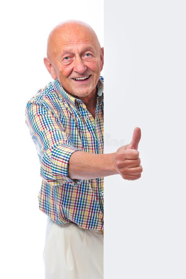 Το ευτυχές χαμογελώντας ανώτερο άτομο κρατά ένα κενό χαρτόνι στοκ εικόνες με δικαίωμα ελεύθερης χρήσης