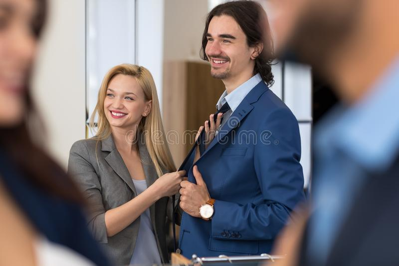 Το ευτυχές χαμογελώντας επιχειρησιακό άτομο δοκιμάζει το νέο κοστούμι με τη νέα θηλυκή βοήθεια πωλητών στοκ φωτογραφία με δικαίωμα ελεύθερης χρήσης