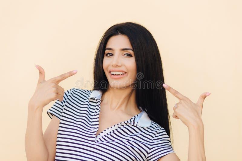 Το ευτυχές χαμογελώντας θηλυκό brunette δείχνει στο στόμα, έχει τη θετική έκφραση, δείχνει στο στόμα με το ευρύ χαμόγελο, έχει το στοκ φωτογραφίες με δικαίωμα ελεύθερης χρήσης