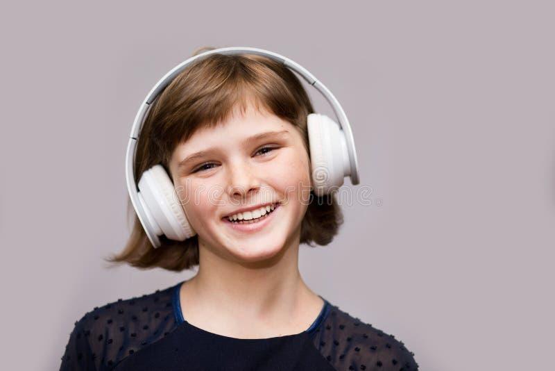 Το ευτυχές χαμογελώντας παιδί απολαμβάνει ακούει τη μουσική στα ακουστικά πέρα από το λευκό στοκ εικόνα με δικαίωμα ελεύθερης χρήσης