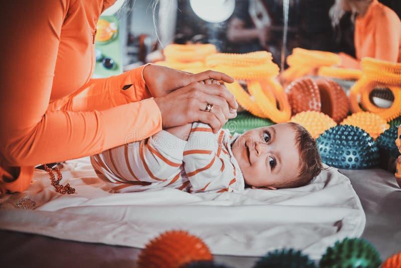 Το ευτυχές χαμογελώντας χαριτωμένο μωρό βρίσκεται στον ειδικό πίνακα που περιβάλλεται από τα ortopedic παιχνίδια στοκ φωτογραφία