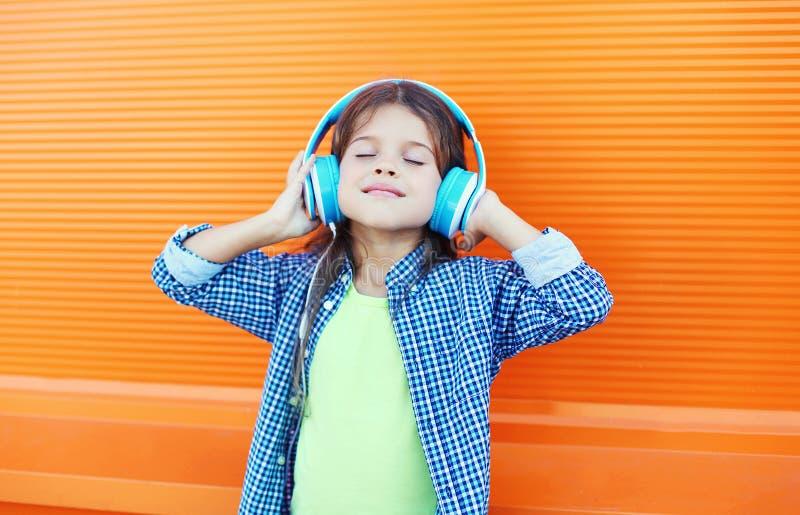 Το ευτυχές χαμογελώντας παιδί απολαμβάνει ακούει τη μουσική στα ακουστικά πέρα από το ζωηρόχρωμο πορτοκάλι στοκ φωτογραφία με δικαίωμα ελεύθερης χρήσης