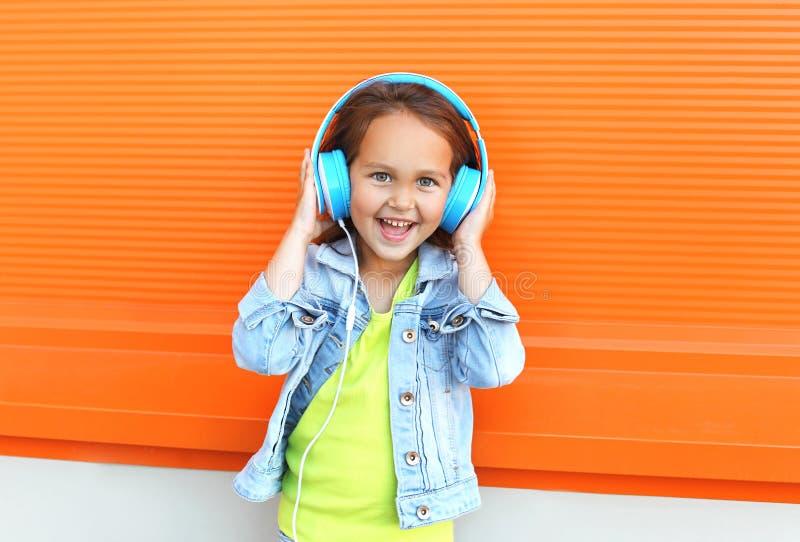 Το ευτυχές χαμογελώντας παιδί απολαμβάνει ακούει τη μουσική στα ακουστικά στοκ φωτογραφία