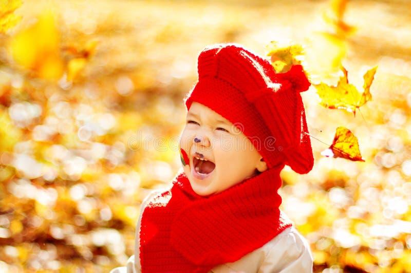 Το ευτυχές χαμογελώντας παιδί στο πάρκο φθινοπώρου, πέφτει κίτρινα φύλλα στοκ εικόνα