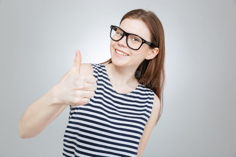 Το ευτυχές όμορφο έφηβη γυαλιών φυλλομετρεί επάνω στοκ εικόνες