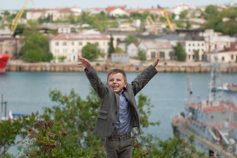 Το ευτυχές όμορφο μικρό παιδί σε ένα σακάκι αύξησε τα χέρια του επάνω στο θαλάσσιο λιμένα στοκ φωτογραφίες με δικαίωμα ελεύθερης χρήσης