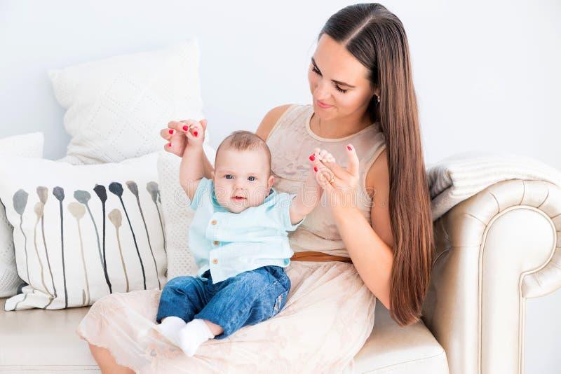 Το ευτυχές mom έβαλε έναν μικρό γιο στην περιτύλιξή της και τα παιχνίδια με τον στοκ εικόνα