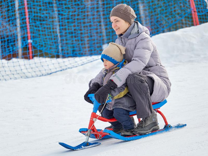 Το ευτυχές mom με το γιο οδηγά ένα έλκηθρο από το βουνό στοκ εικόνες