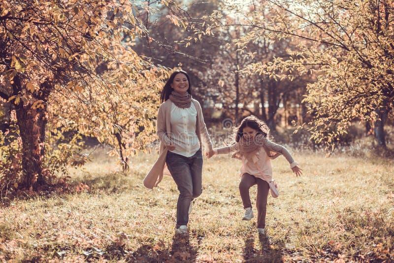 Το ευτυχές mum και η κόρη παίζουν το πάρκο φθινοπώρου στοκ εικόνα με δικαίωμα ελεύθερης χρήσης
