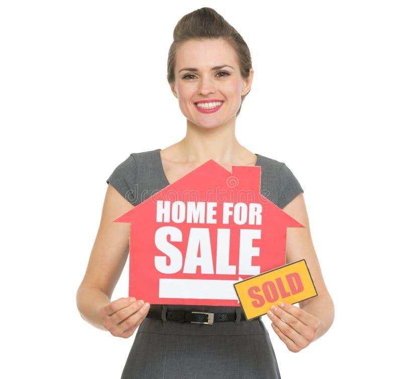 Το ευτυχές realtor που εμφανίζει σπίτι για την πώληση πώλησε το σημάδι στοκ εικόνες