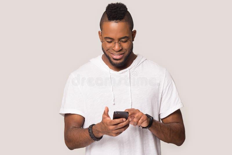 Το ευτυχές smartphone λαβής ατόμων αφροαμερικάνων λαμβάνει το καλό μήνυμα στοκ εικόνα με δικαίωμα ελεύθερης χρήσης