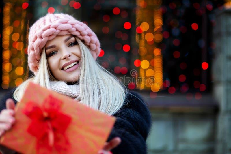 Το ευχάριστο ξανθό κορίτσι που φορά το παλτό γουνών και την πλεκτή ΚΑΠ τραβά το α στοκ εικόνα με δικαίωμα ελεύθερης χρήσης
