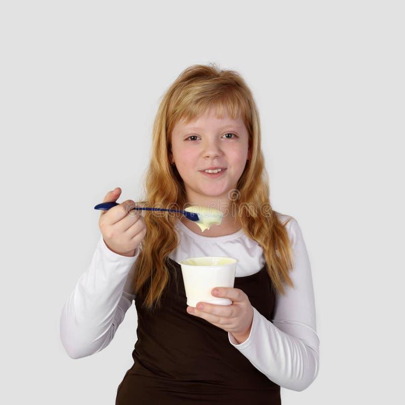 Το εφηβικό redhead κορίτσι τρώει το γιαούρτι στοκ φωτογραφίες