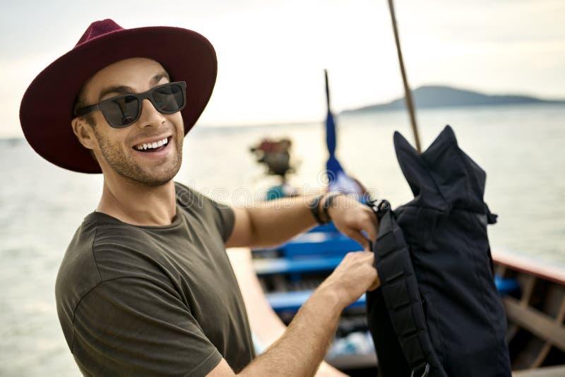 Το εύθυμο άτομο με τις καλαμιές κρατά το σακίδιο πλάτης του κοντά στην ξύλινη βάρκα στοκ εικόνα με δικαίωμα ελεύθερης χρήσης
