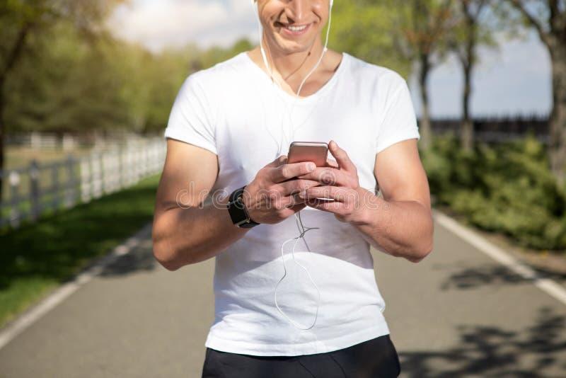 Το εύθυμο άτομο στα ακουστικά απολαμβάνει τον ήχο στο τηλέφωνο στοκ φωτογραφία με δικαίωμα ελεύθερης χρήσης