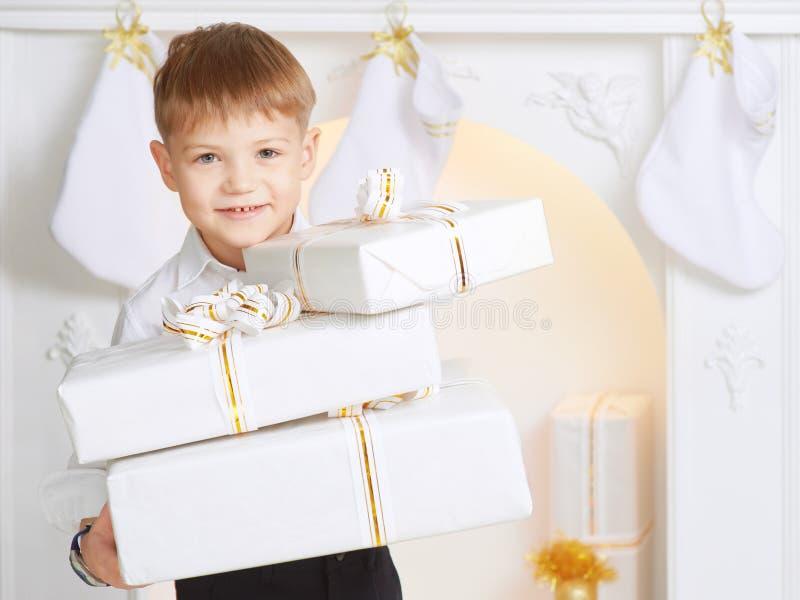 Το εύθυμο αγόρι κρατά πολύ άσπρο δώρο κιβωτίων στο υπόβαθρο του τ στοκ φωτογραφίες
