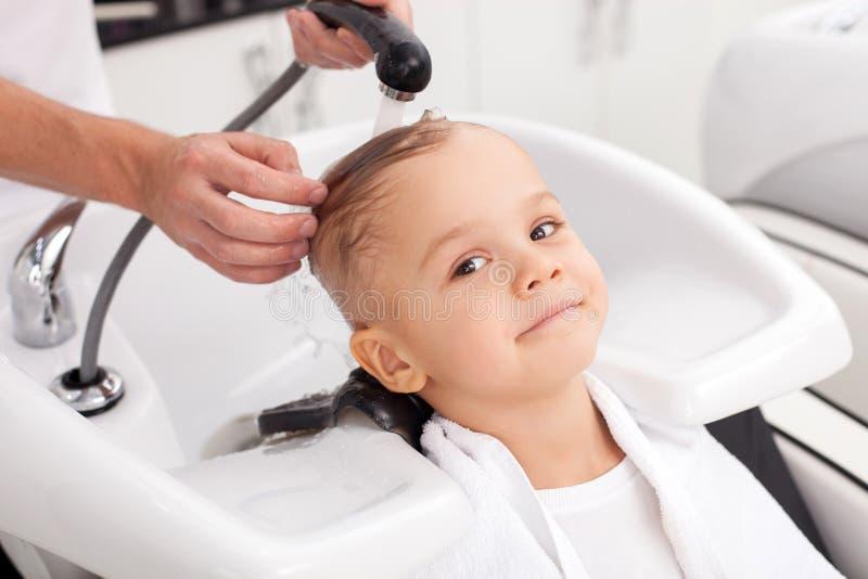 Το εύθυμο αγόρι πλένει την τρίχα στο σαλόνι στοκ εικόνες