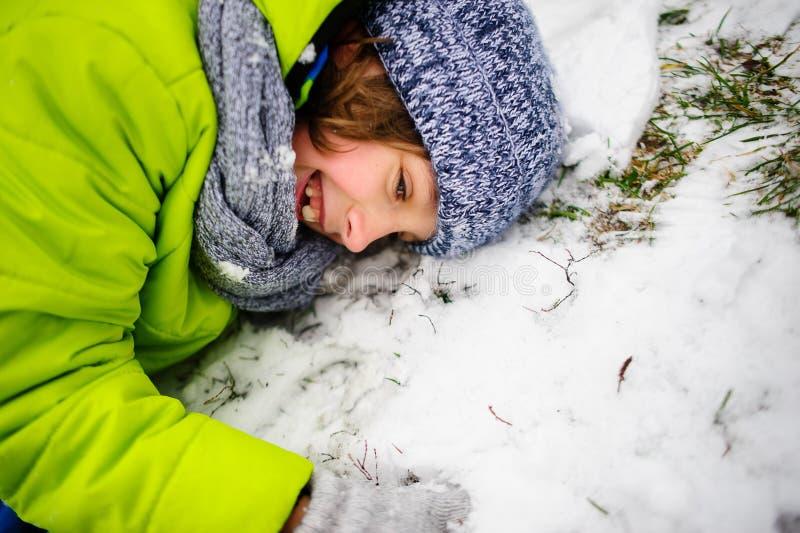 Το εύθυμο αγόρι της ηλικίας σε ένα φωτεινό κοστούμι σκι βρίσκεται στο χιόνι στοκ φωτογραφία με δικαίωμα ελεύθερης χρήσης