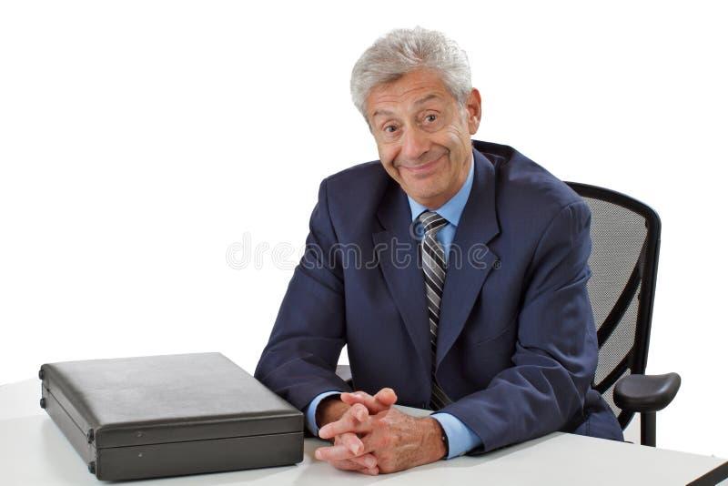 Το εύθυμο ανώτερο επιχειρησιακό άτομο κάθεται στο γραφείο στοκ εικόνες με δικαίωμα ελεύθερης χρήσης