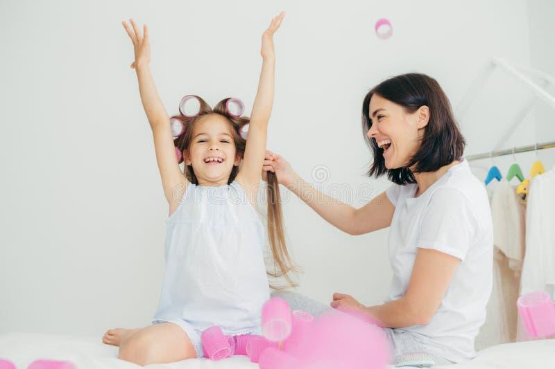Το εύθυμο θηλυκό brunette κάνει την τρίχα της κόρης της που έχει ευτυχή στοκ φωτογραφία