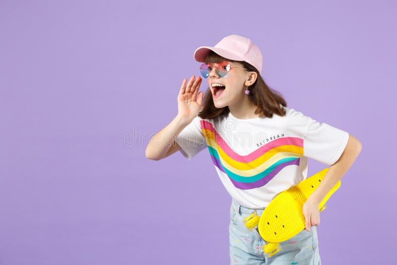Το εύθυμο κορίτσι εφήβων στα ζωηρά ενδύματα, eyeglasses κρατά skateboard, κοιτάζοντας κατά μέρος κραυγάζοντας με τη χειρονομία χε στοκ φωτογραφίες
