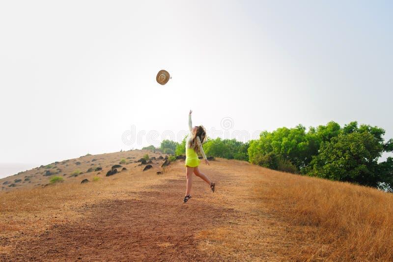 Το εύθυμο κορίτσι με τα μακρυμάλλη άλματα και ρίχνει το καπέλο αχύρου στον αέρα Νέα γυναίκα brunette στους σύντομους περιπάτους φ στοκ εικόνα με δικαίωμα ελεύθερης χρήσης