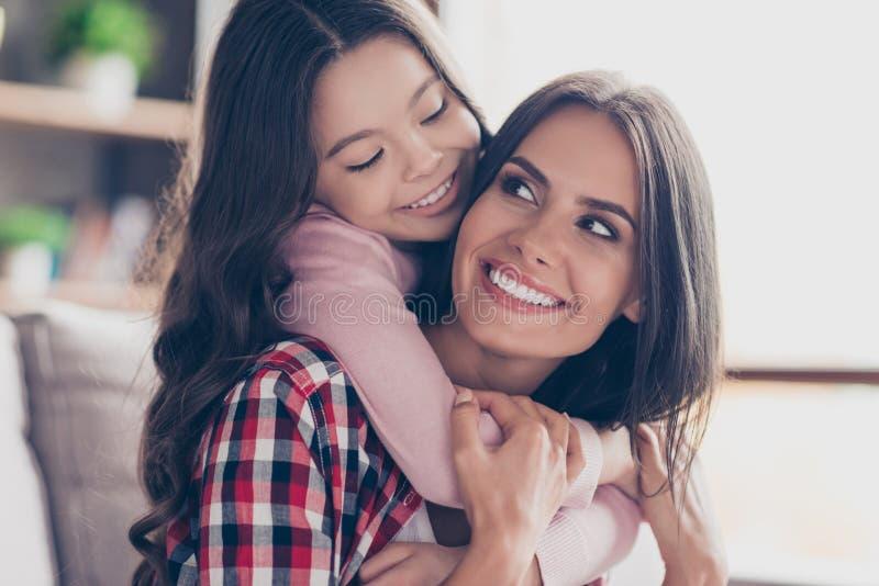 Το εύθυμο μικρό κορίτσι με τη μακριά σκοτεινή τρίχα αγκαλιάζει το λαιμό mum της ` s στοκ εικόνες