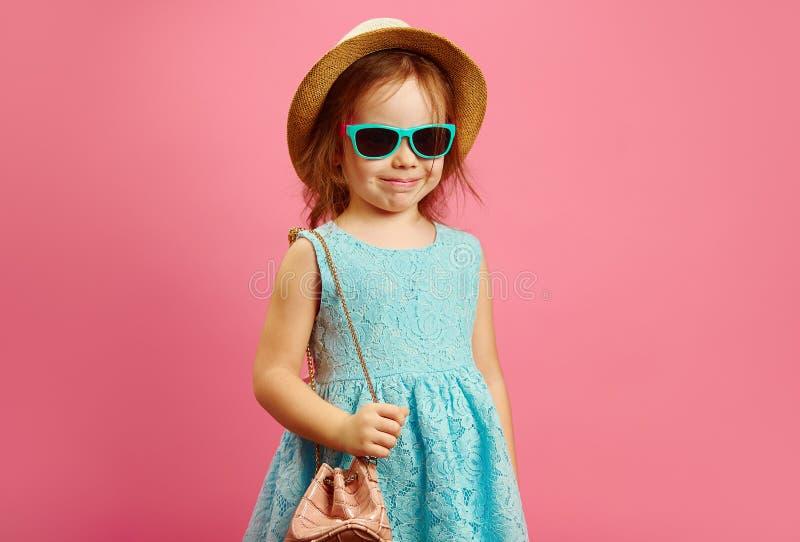 Το εύθυμο μικρό κορίτσι στα ενδύματα παραλιών και η τσάντα, στάσεις πέρα από απομονωμένο το ροζ υπόβαθρο, εκφράζουν τη χαρά και τ στοκ εικόνες